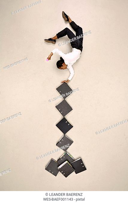 Businesswoman balancing upside down on folders