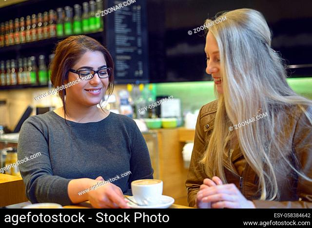 Young waitress serving a cup of coffee to a pretty young female customer in a restaurant or pub placing the cup on the table with a smile