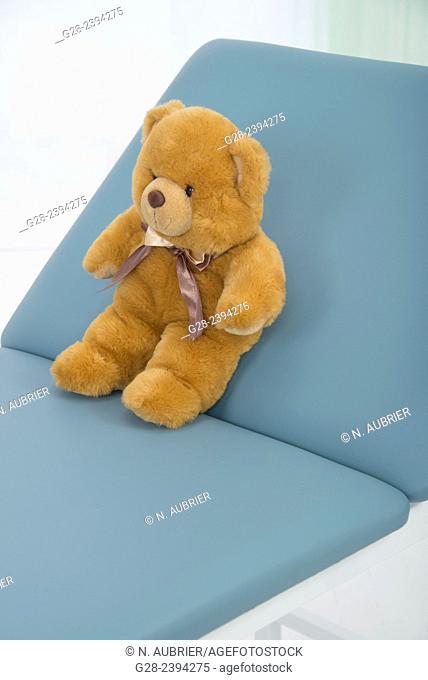Teddy bear on blue medical examination couch