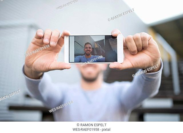 Smiling man taking selfie with cell phone, close-up