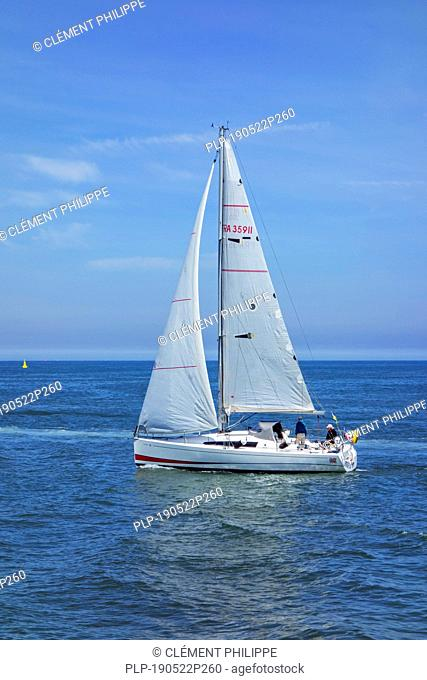 Two elderly sailors in sailing boat / sailboat at sea
