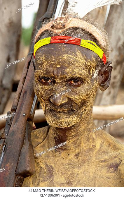 Karo warrior with body paintings, colorful headband and a rifle on the shoulder, South Omo Valley, Southern Ethiopia