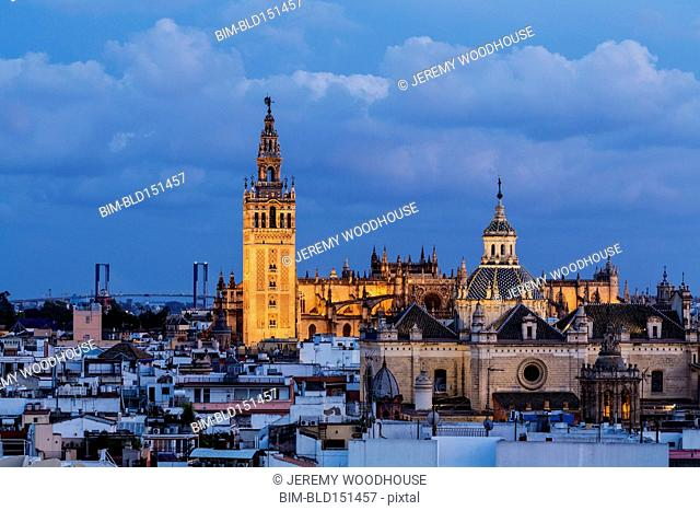 Illuminated cathedral over Seville cityscape, Andalusia, Spain