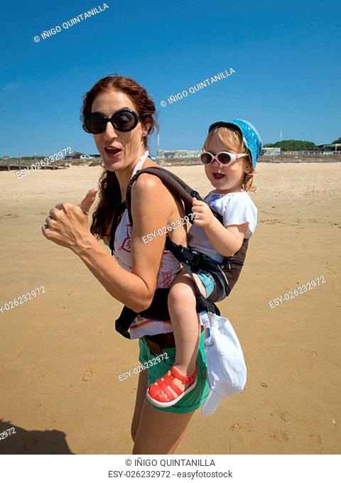 brunette woman mother carrying in backpack rucksack her two year blonde baby old with blue hat white sunglasses with thumb up fingers singing happy at a beach...