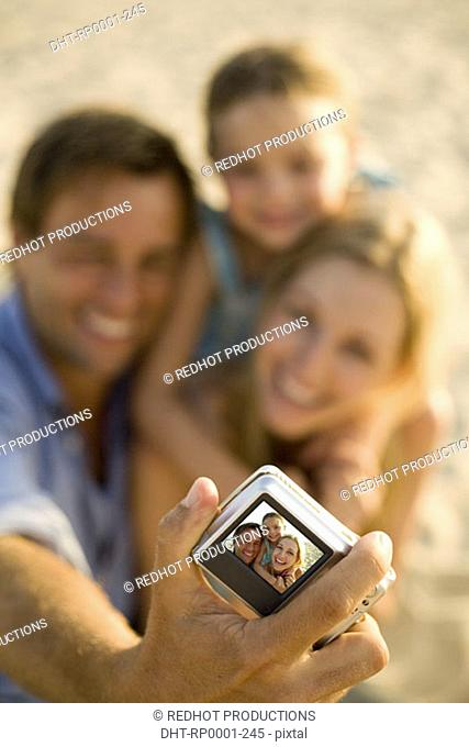 Family on beach, with camera