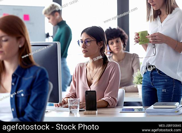 Businesswoman working at computer in an office, boss standing next to her