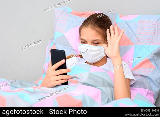 A sick girl lies in bed and communicates with friends online via video-telephone