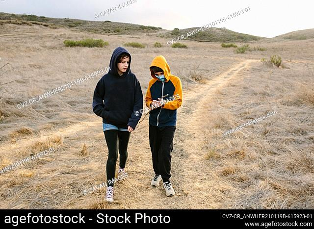 Sister And Brother Walk Along A Hiking Trail In Southern California
