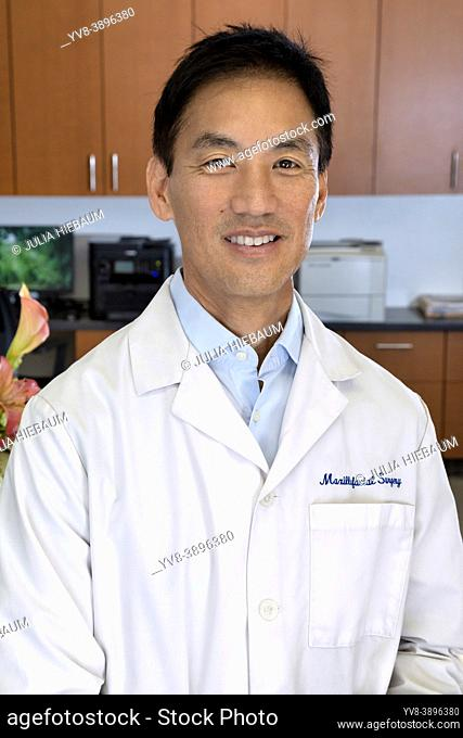 Asian male doctor inside his front desk office