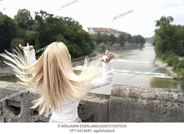 woman shaking hair on bridge over river Isar in Munich, Germany