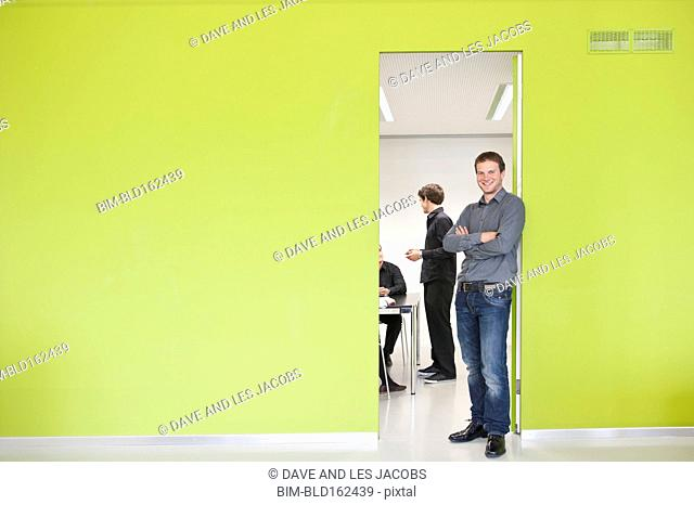 Caucasian businessman smiling at door to office meeting