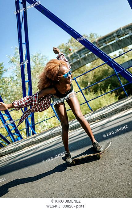 Happy young woman on skateboard on a bridge