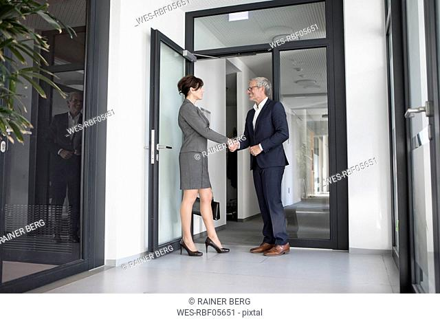 Businessman and businesswoman shaking hands in office corridor