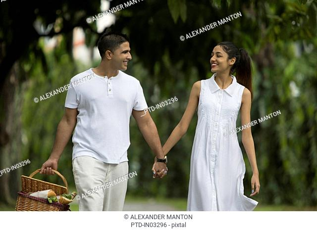 Singapore, Young couple walking along garden path with picnic basket