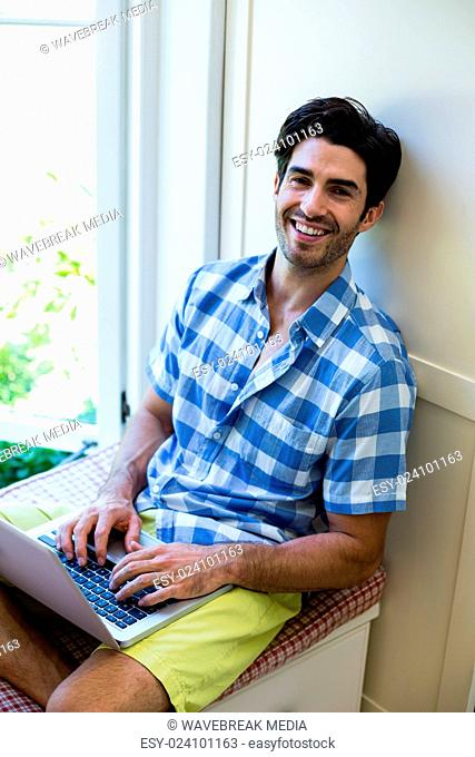 Portrait of man sitting on bed and using laptop