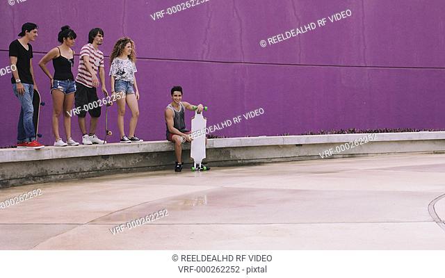 Teenage girl enjoying skateboarding and giving high-five to friends on street