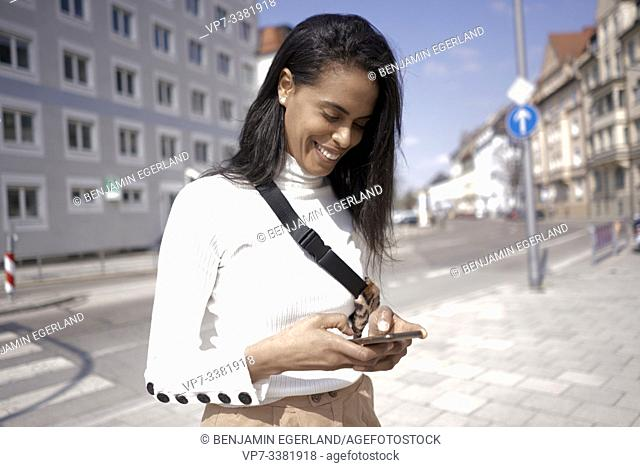 Brazilian woman on the street, using smartphone, Munich, Germany
