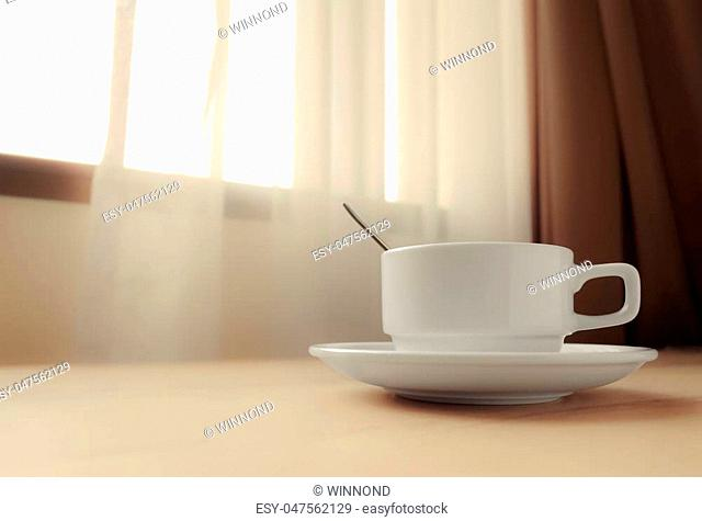 white coffee cup by the window