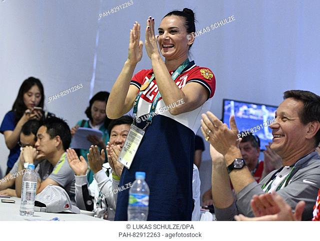 Athlete Yelena Isinbayeva (C) of Russia reacts next to President of Russian Olympic Committee Alexander Zhukov (R) during the IOC Athletes Commission Election...
