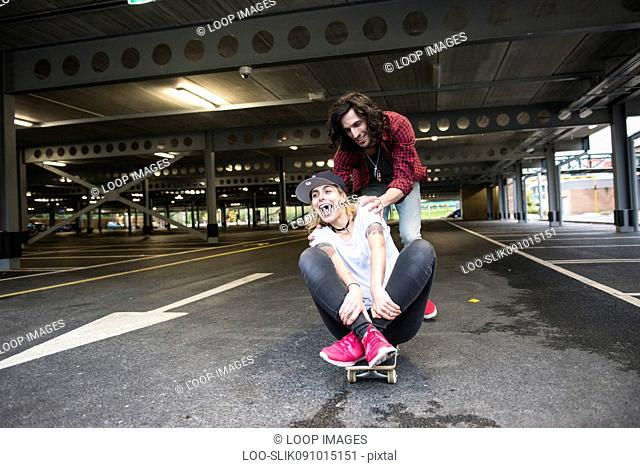 A cool young couple having fun with a skateboard