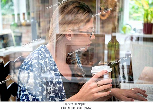 Pregnant mid adult woman reading a book at kitchen table