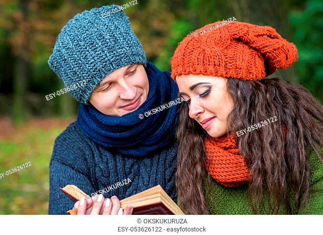 loving couple reads a book in the autumn garden
