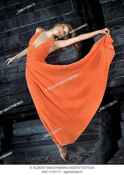 Beautiful woman in long orange dress leaning against black granite wall