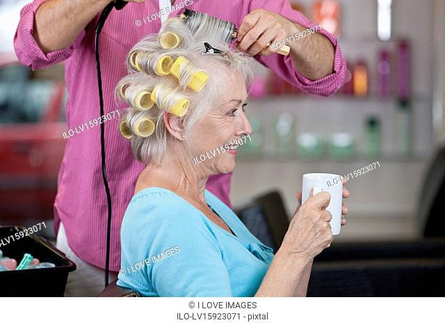 A senior woman drinking a hot beverage whilst having her hair dried, close up