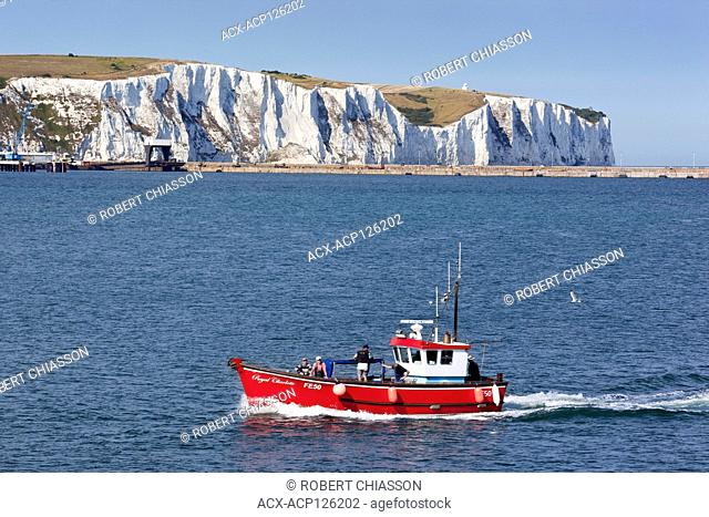 Famous white cliffs of Dover while, in the foreground, is a charter boat returning to the city's harbour. Dover, United Kingdom
