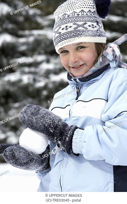 Young girl making snowball