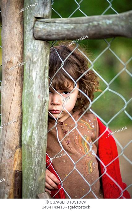 Young girl behind fence