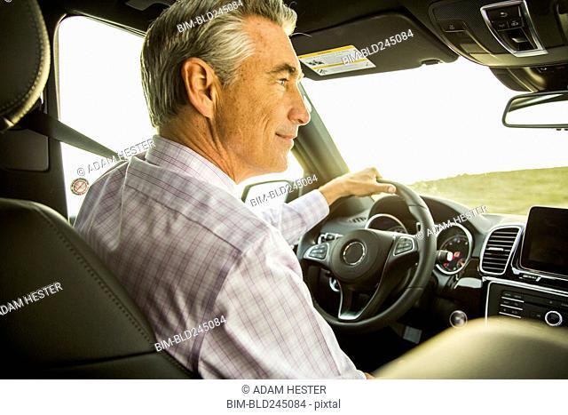 Smiling Caucasian businessman driving car