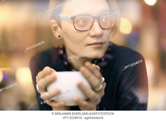 woman holding coffee cup, indoors behind glass window in café, in Munich, Germany