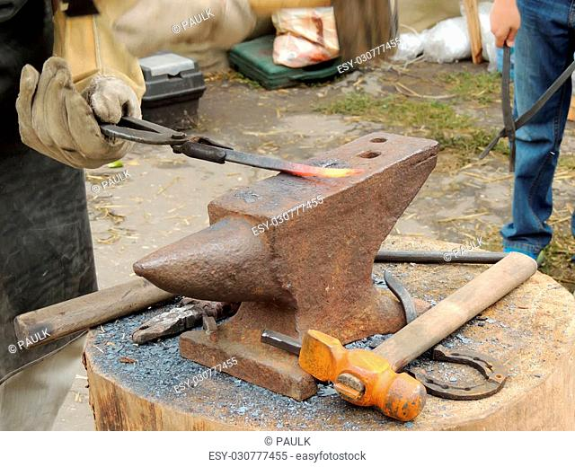 Smith handles the iron bar on the anvil