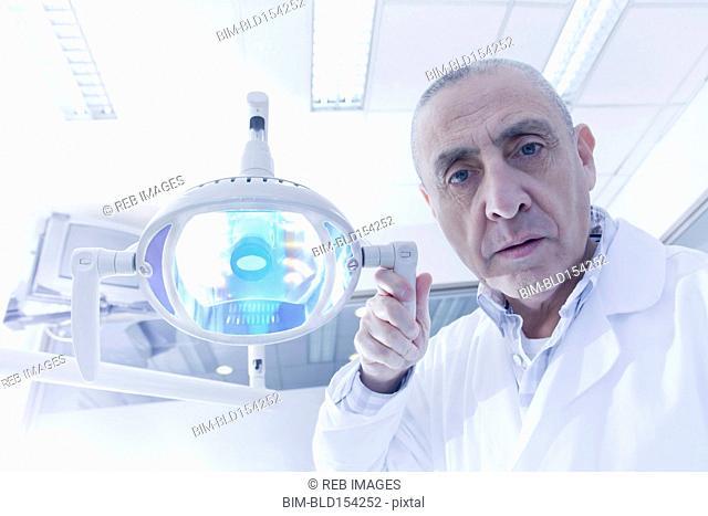 Hispanic dentist holding lamp in office