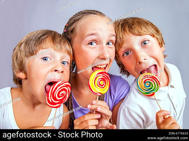 Group of happy children eating candy