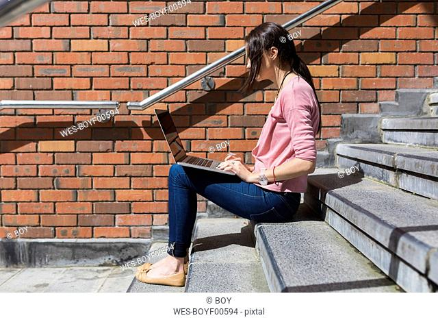 Woman sitting on stairs working with laptop