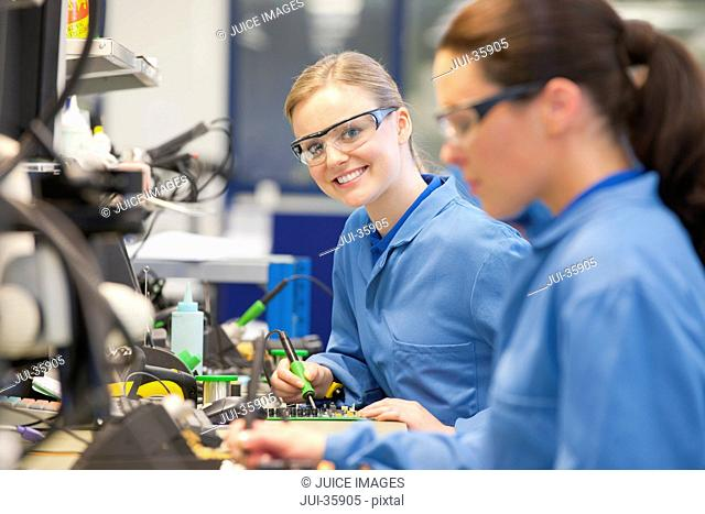 Portrait of smiling technician soldering circuit board on production line in manufacturing plant