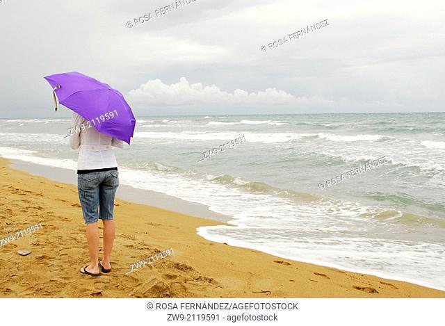 Young woman walking with purple umbrella, Las Marinas Beach, Denia, province of Alicante, Comunidad Valenciana, Spain