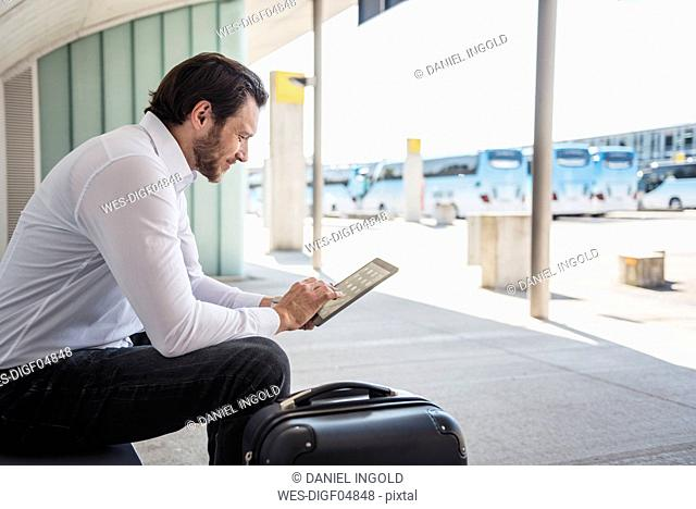 Smiling businessman with suitcase sitting at bus terminal using tablet