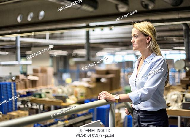 Businesswoman in factory overlooking storehouse