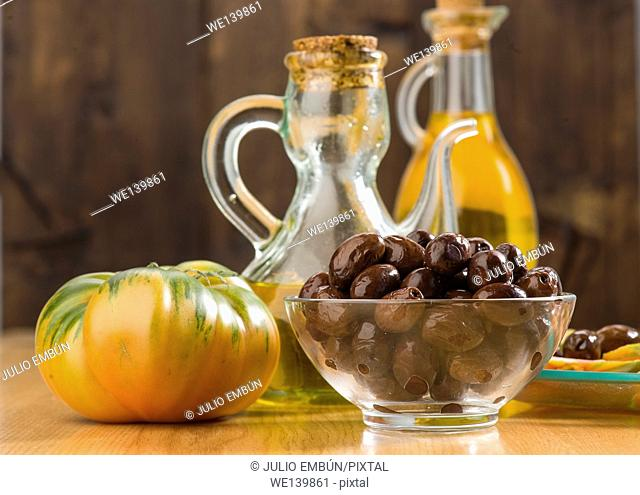 bowl of black olives and oil can with olive oil