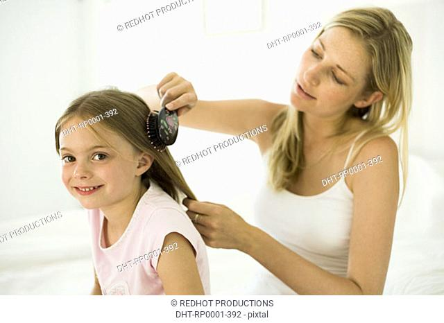 Mother and daughter, brushing hair