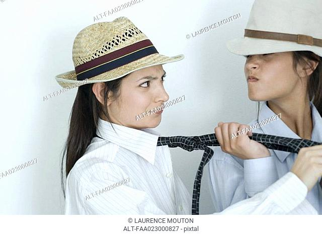 Two young female friends dressed in button down shirts, ties and hats, one pulling on the other's tie