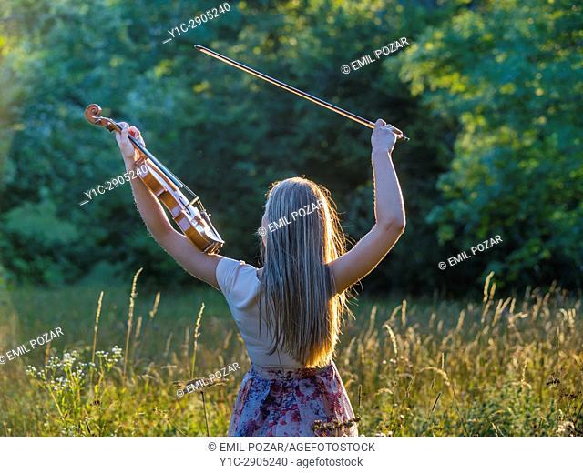 Young female violinist in nature. Croatia