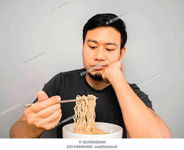 Poor Asian man feel boring with the same old instant noodle