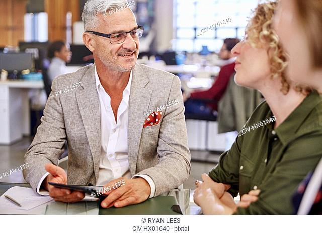 Business people with digital tablet talking in meeting