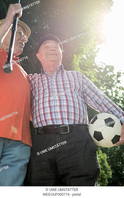 Two old friends walking in the park with football