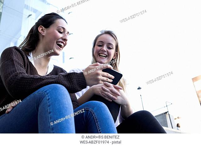 Two friends sitting on stairs using cell phone