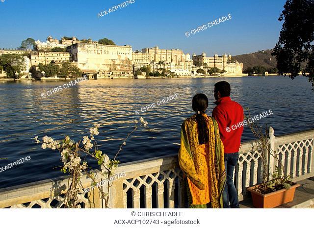 Visitors admire City Palace on Lake Pichola, Udaipur, Rajastan, India
